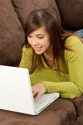 A woman laying down on couch using a laptop